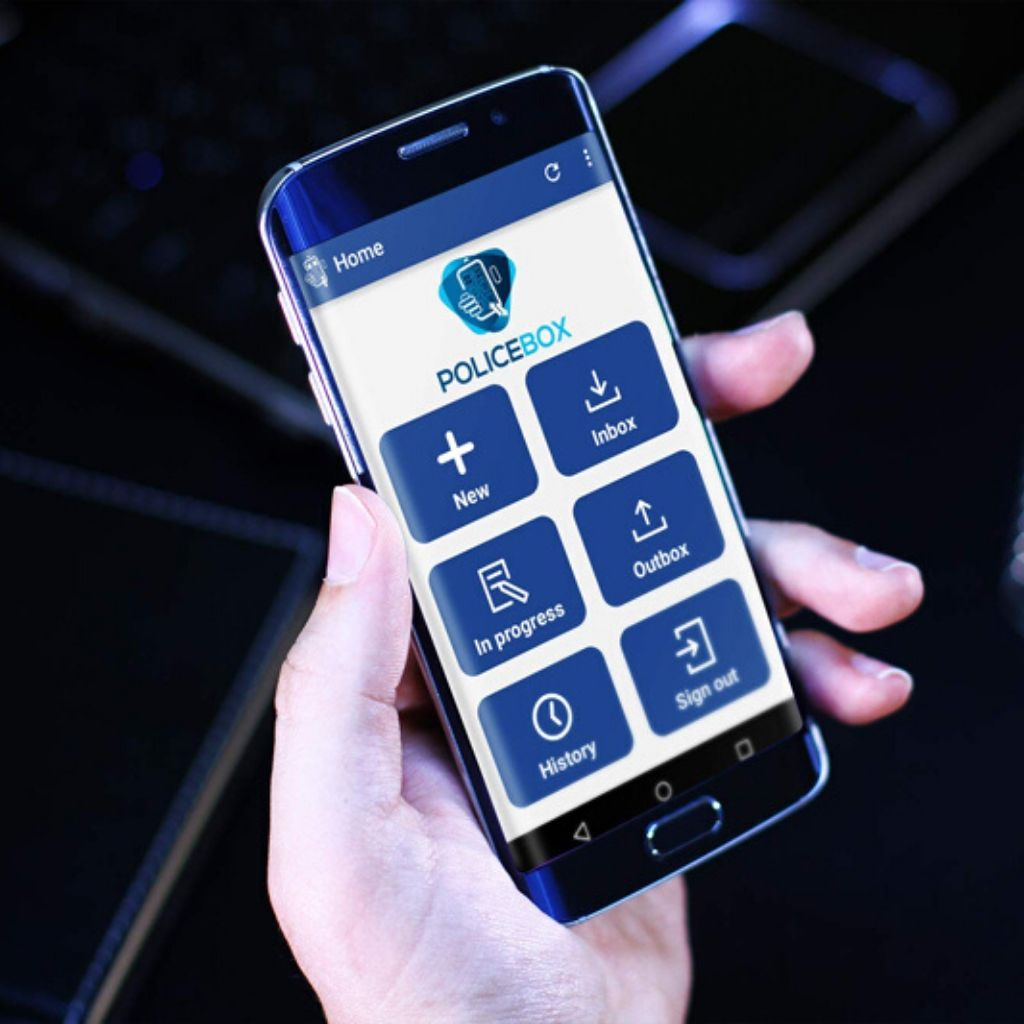 Hand holding mobile phone displaying Coeus software mobile app