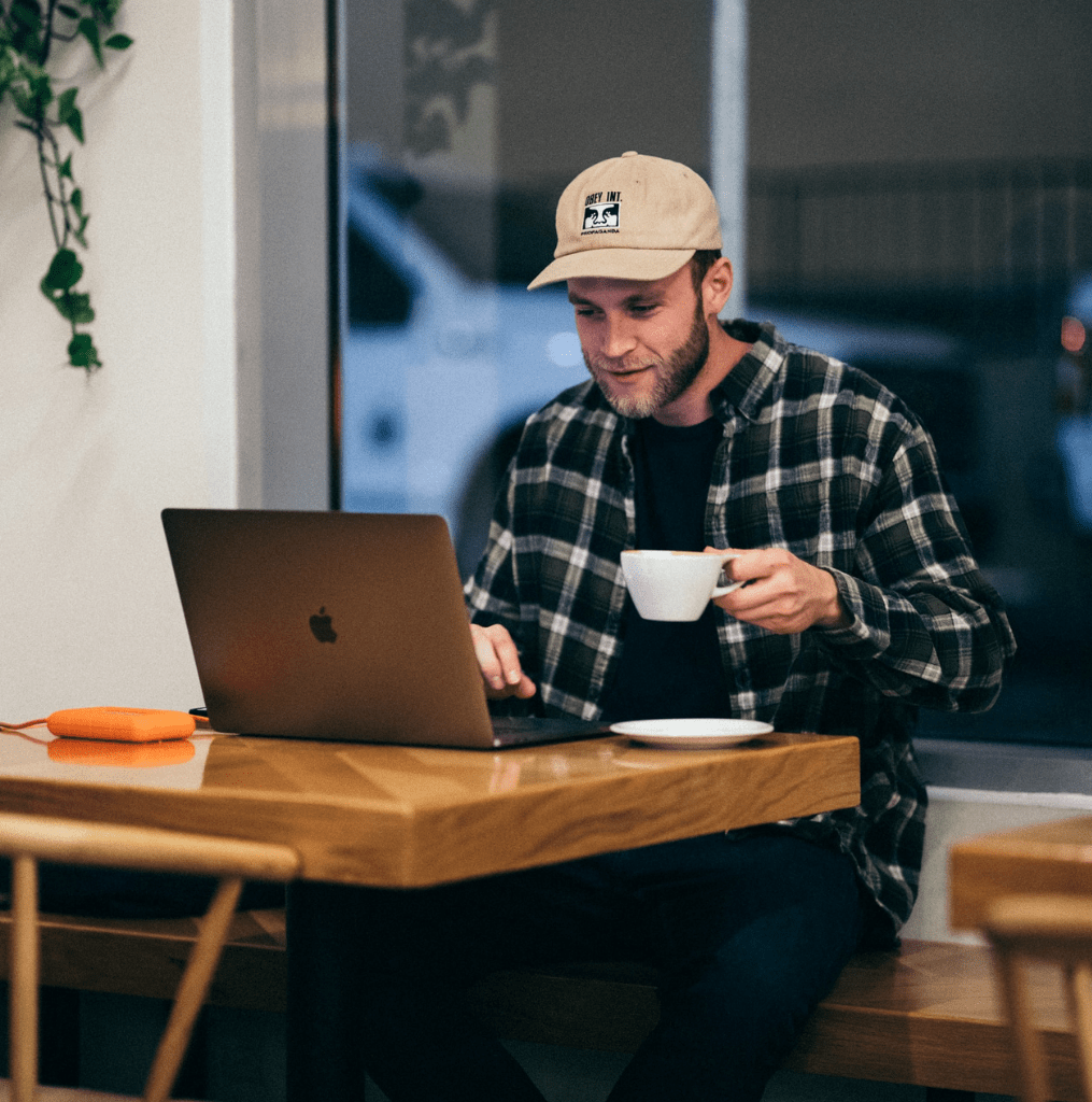 Man sat at desk with coffee and laptop learning how to become an app creator