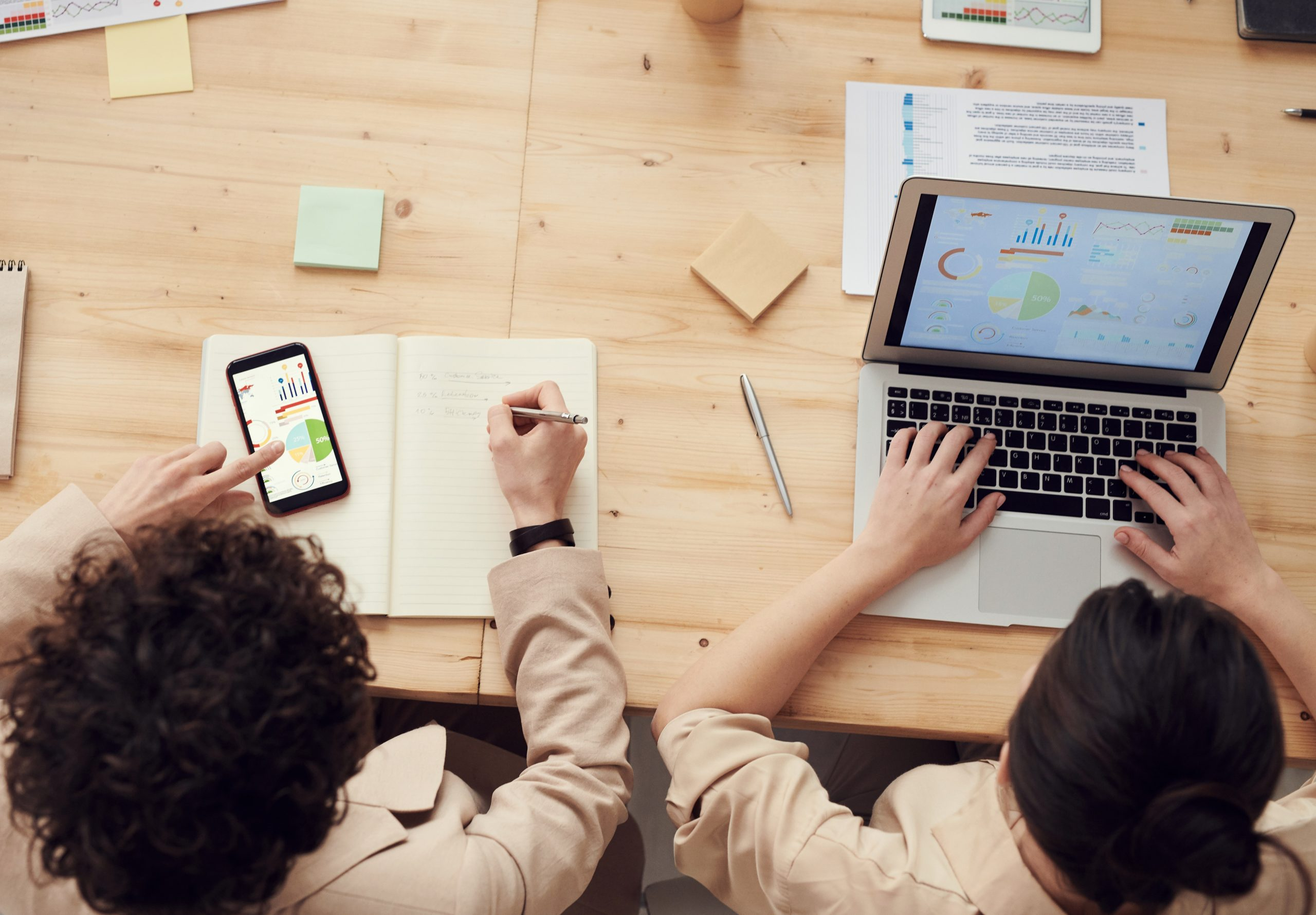 Two people sat a desk automating tasks with their bespoke business work flow app