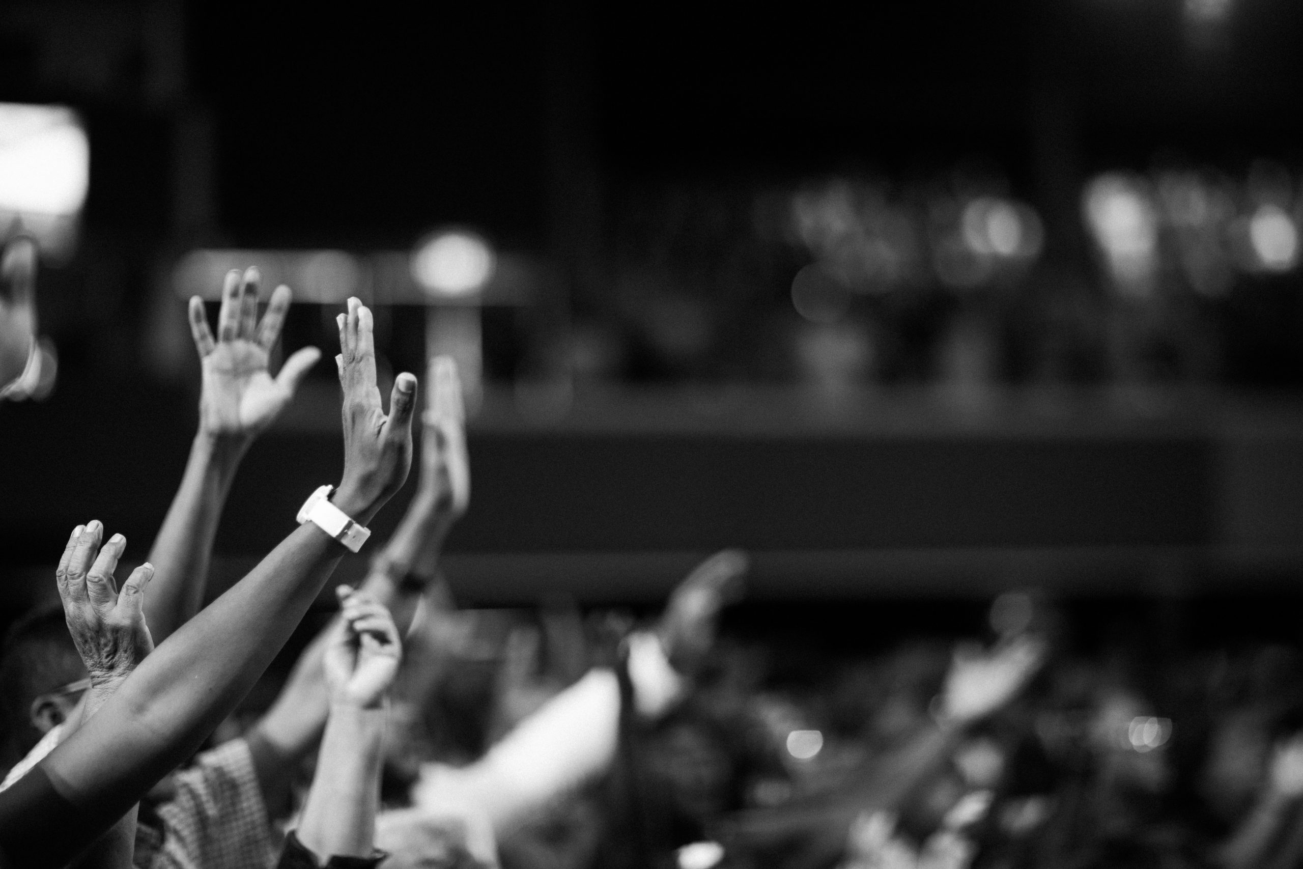Multiple hands being raised in a church setting