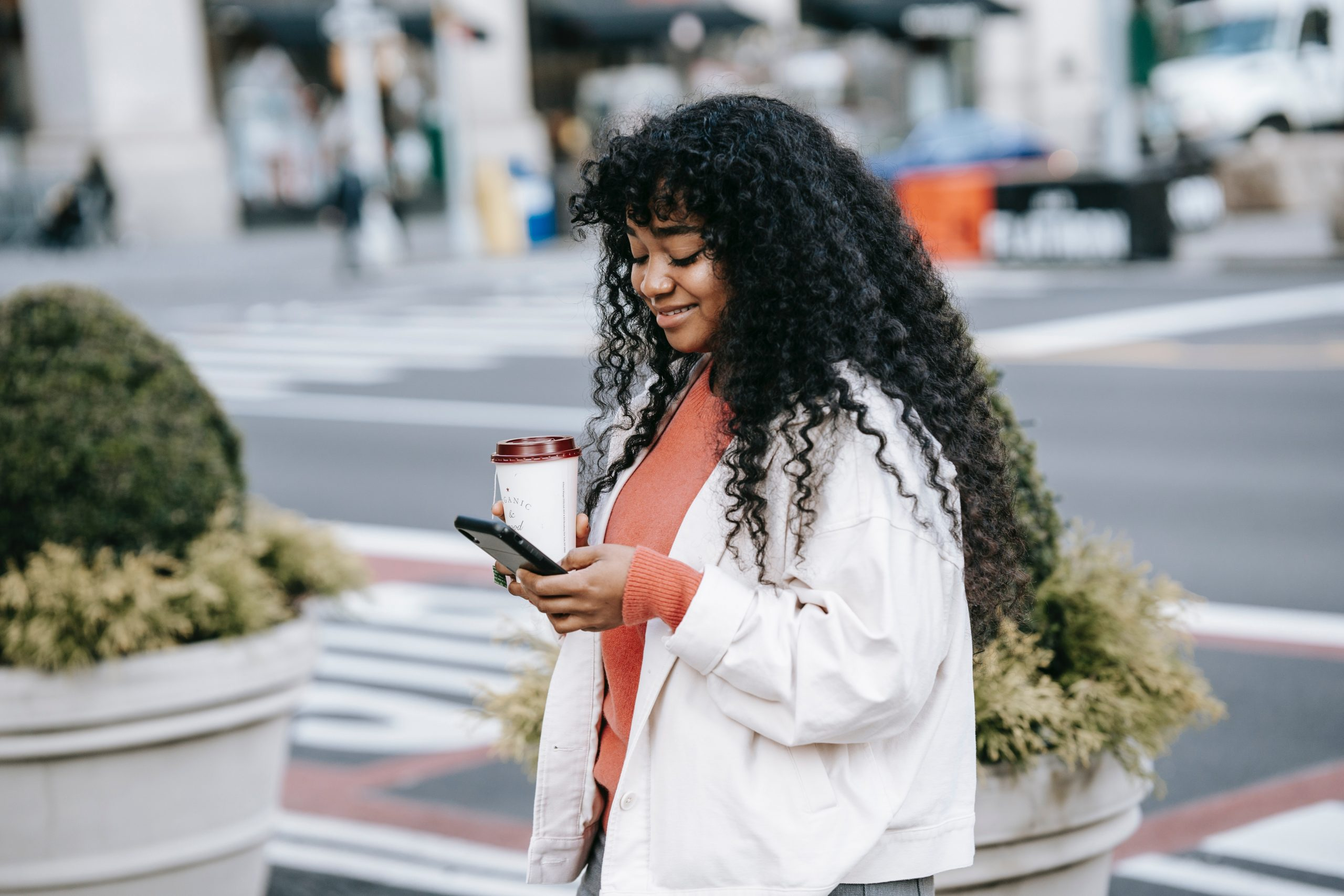 Girl walking on road holding a coffee and mobile phone looking at church mobile app